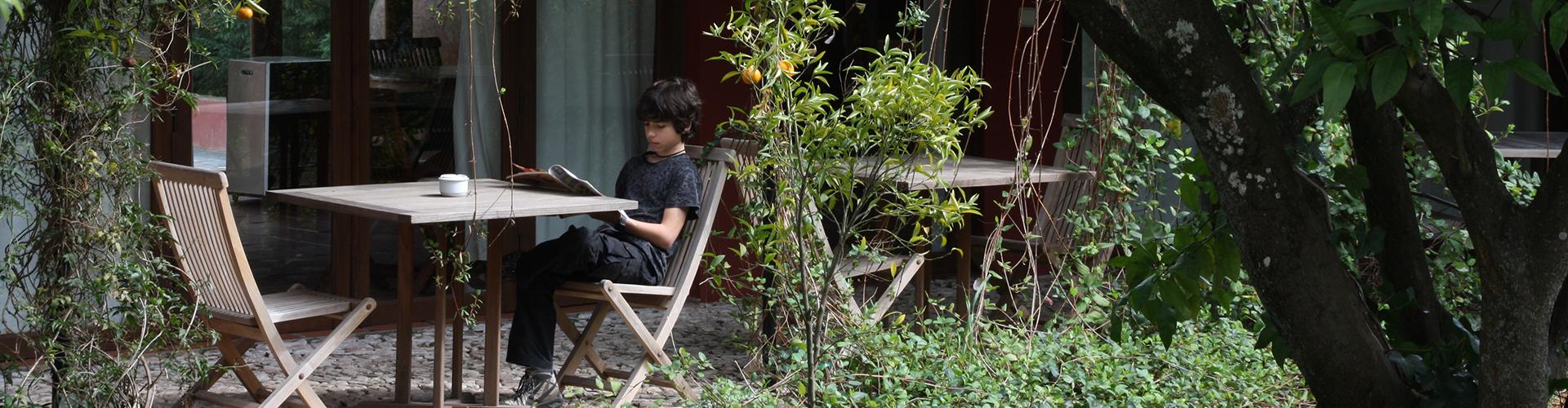 CASA DO TERREIRO DO POÇO. Leyendo un libro en el jardín.